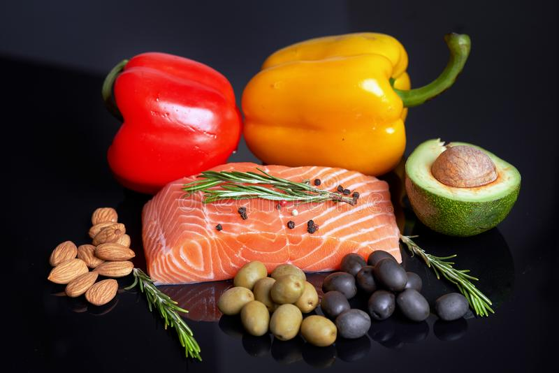 A slice of raw salmon fillet with a sprig of rosemary, red and yellow sweet peppers, almond nuts, green and black olives and slice. D avocado fruit. Healthy food royalty free stock photography