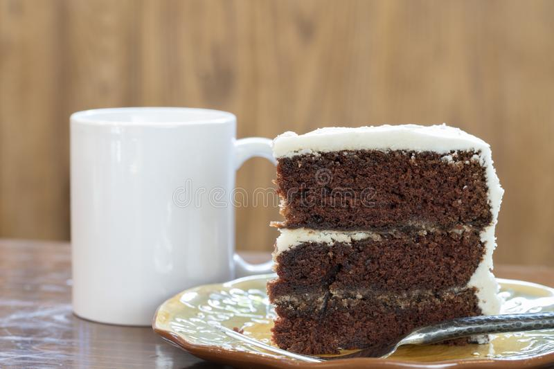A slice of rich moist 3 layer chocolate cake on a plate royalty free stock photos