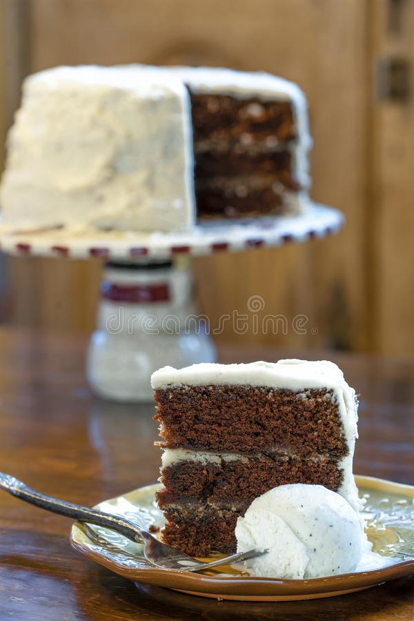 A slice of rich moist 3 layer chocolate cake on a plate stock photos