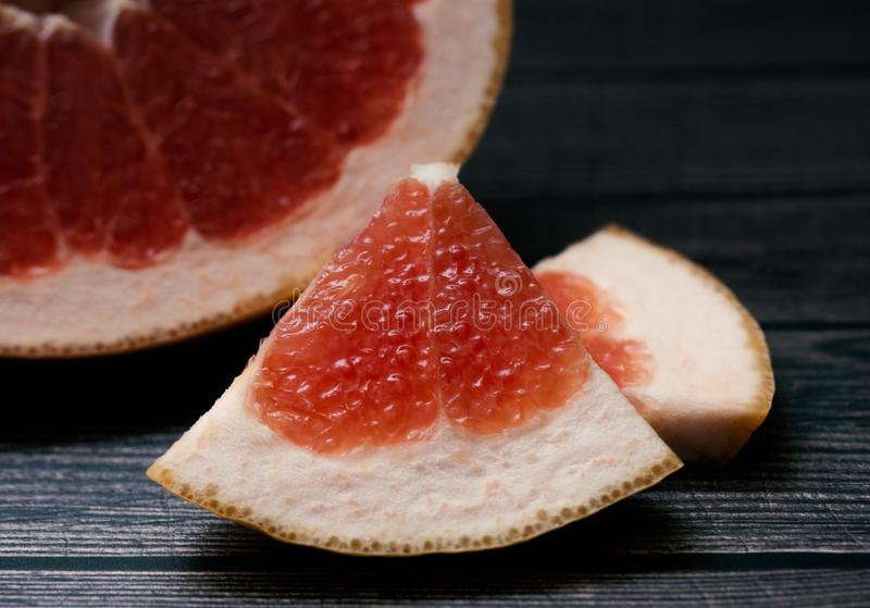 A slice of ripe red grapefruit on a dark gray background close-up. Sour fruit. Slice of juicy citrus. Healthy food for raw foodists and vegetarians royalty free stock photos