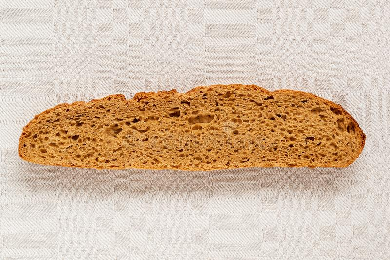 Slice of rye bread with an appetizing crispy brown crust on a gray linen tablecloth. Tasty, usefull and nutritious royalty free stock images