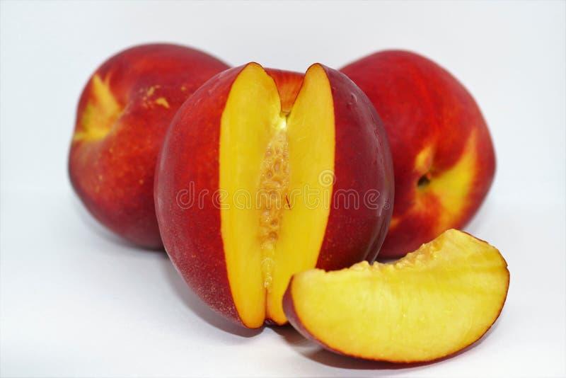 A slice of sweet nectarine. Ripe red nectarine  on white background. Delicious and sweet nectarine royalty free stock image