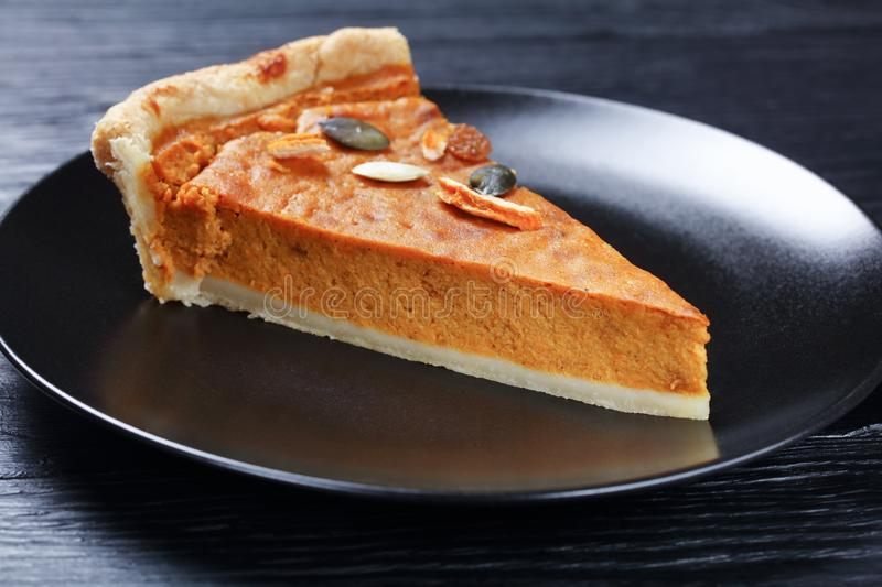 A slice of Sweet potato pie, top view. A slice of Sweet potato pie decorated with  pumpkin seeds on a black plate on a wooden table, horizontal view from above royalty free stock image