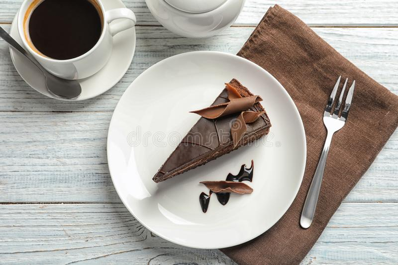 Slice of tasty chocolate cake and cup of coffee served. On wooden table, top view royalty free stock images