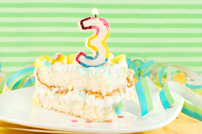 Slice of third birthday cake. With lit candle, confetti, and ribbon royalty free stock images