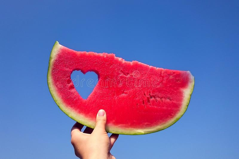 A slice of watermelon and heart against the bright summer sky in the girl`s hand. stock photos