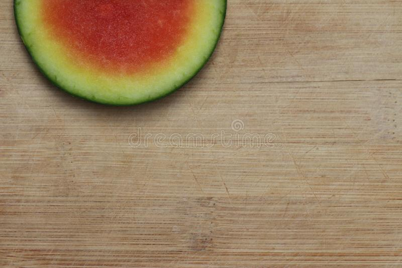 Slice of watermelon offset on the top of a worn bamboo cutting board stock photos