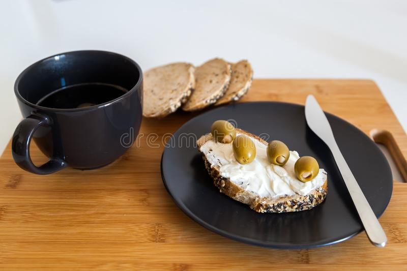 Slice of Whole Grain Bread with cheese and olives. Shot of Whole Grain Bread with cheese and olives stock photo