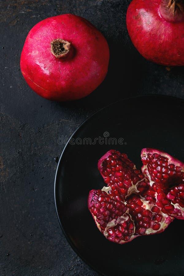 Slice and whole pomegranates royalty free stock images