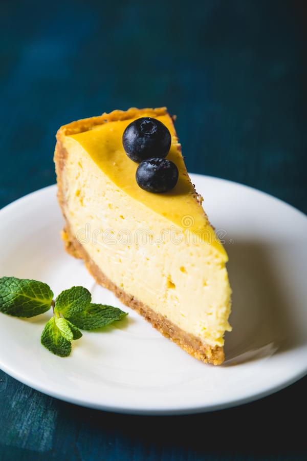 A slice of yellow cheesecake with mango and fresh blueberries stock photo