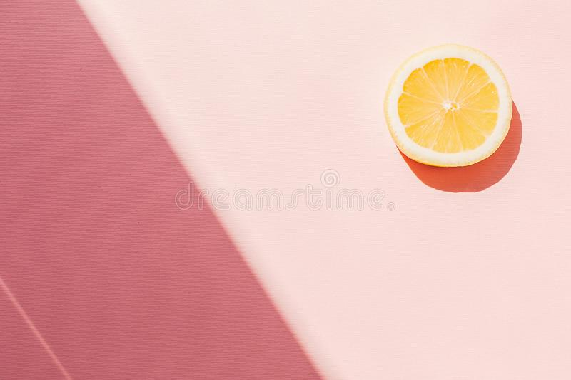 Slice of yellow lemon on trendy pink paper background flat lay, royalty free stock image