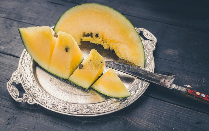 Slice yellow watermelon on a silver plate and knife on a dark wooden background stock photography