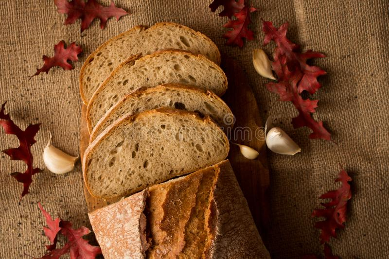 A fresh loaf of bread. Sliced ​​fresh bread in composition with aun leaves and garlic royalty free stock photos