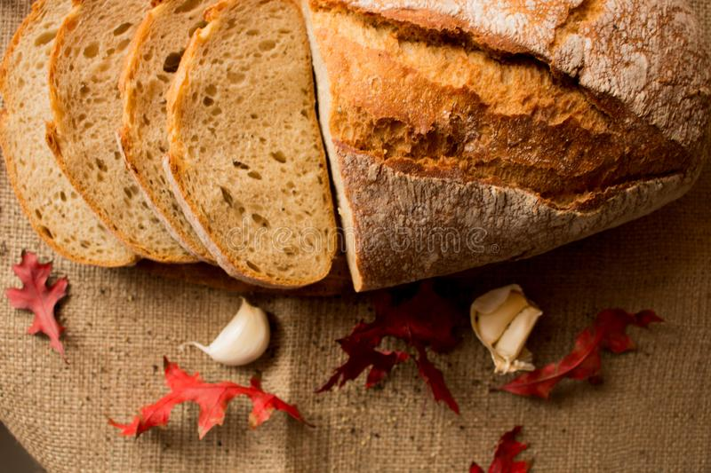 A fresh loaf of bread. Sliced ​​fresh bread in composition with aun leaves and garlic royalty free stock photography