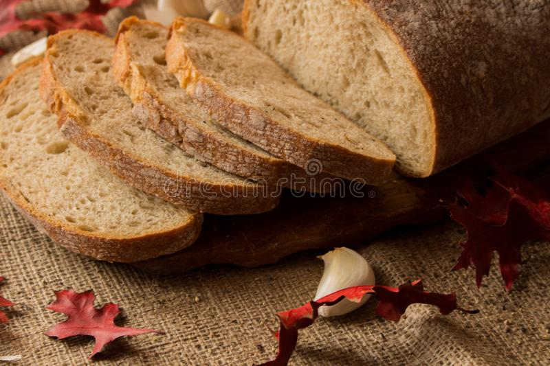 A fresh loaf of bread. Sliced ​​fresh bread in composition with aun leaves and garlic stock photos
