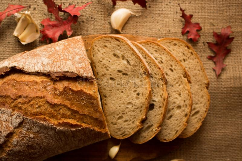 A fresh loaf of bread. Sliced ​​fresh bread in composition with aun leaves and garlic royalty free stock image