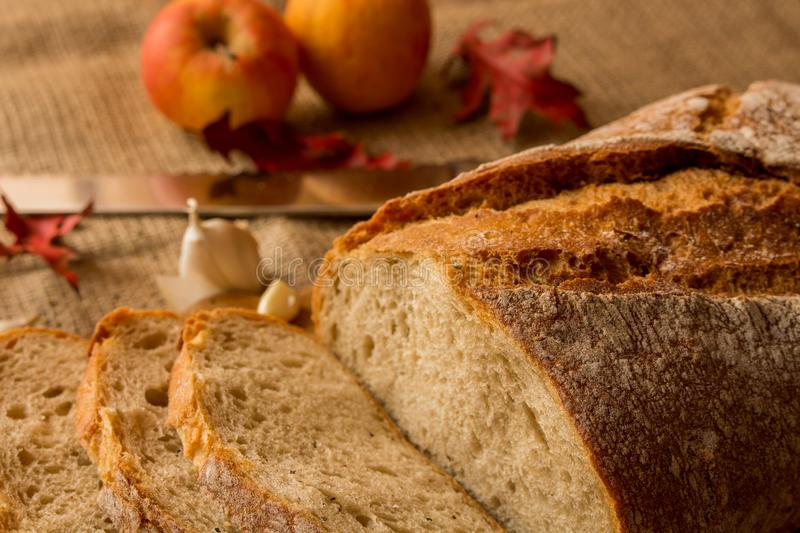 A fresh loaf of bread. Sliced ​​fresh bread in composition with aun leaves and garlic stock photography