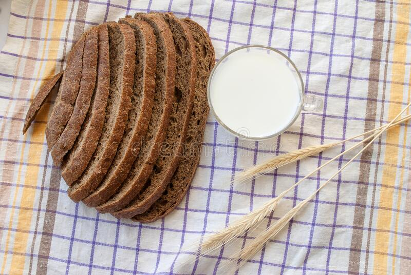 Sliced gray bread, cup of milk, ears of corn. Top view royalty free stock photography