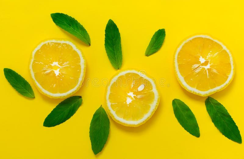 Sliced lemon and mint leaves on a bright yellow background. Background for the design of banners, websites. royalty free stock image