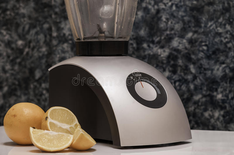 Sliced oranges slices near the blender royalty free stock photography