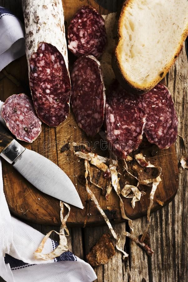 Sliced ​​salami on wooden cutting board with knife royalty free stock photo