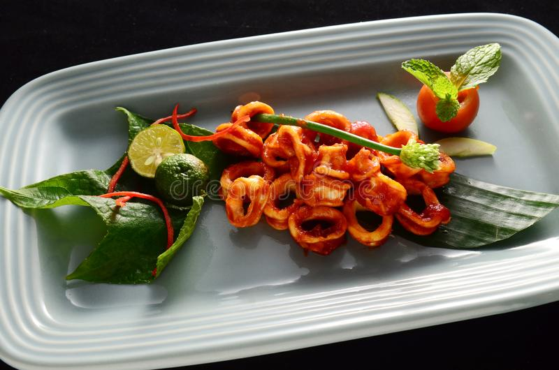 Sliced ​​squid dishes extra spicy sauce, red squid and lime and fresh tomatoes royalty free stock photos