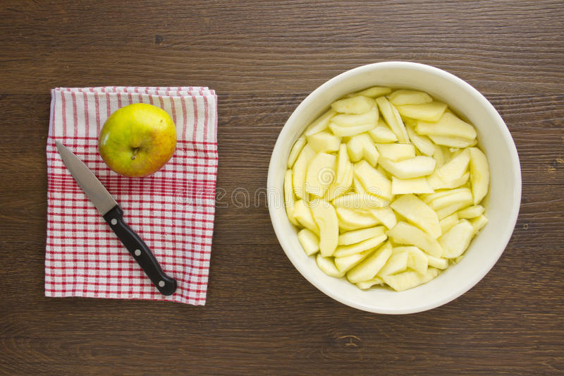 Sliced apples for an apple pie. Freshly peeled and sliced apples sit ready prepared in a bowl of cold water, while a whole apple is ready to be peeled and stock images