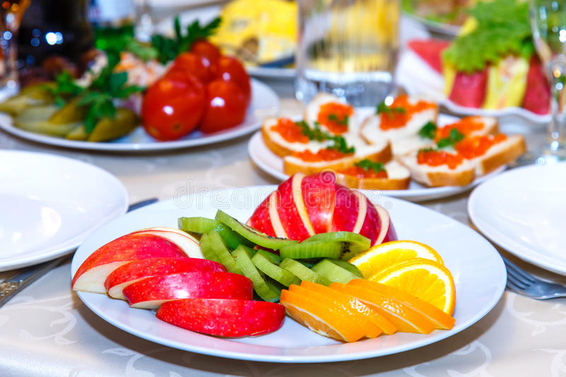 Sliced apples, oranges, marinated tomatoes, cucumbers. And sandwiches with caviar on banquet table royalty free stock image