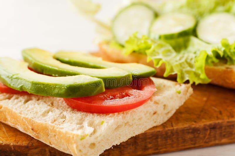 Sliced avocado, tomatoes, cucumber on a fresh ciabatta bread.  royalty free stock image