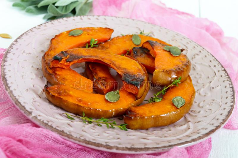 Sliced of baked pumpkin in a honey sauce with aromatic herbs on a ceramic plate. On a white wooden background stock photography
