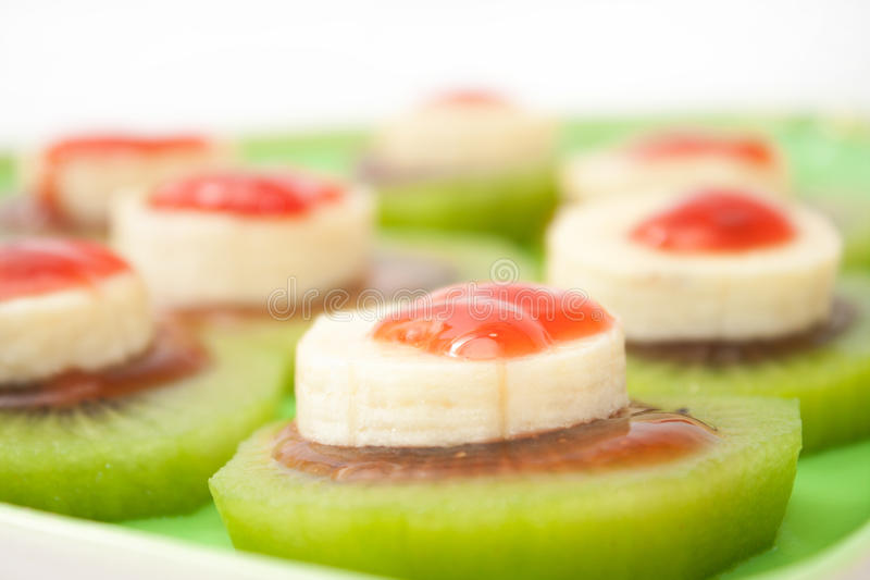 Sliced banana and kiwi with strawberry syrup on the green plate.  royalty free stock photography