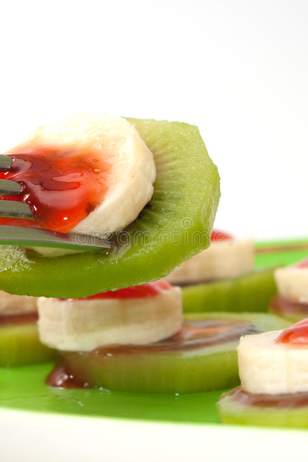 Sliced banana and kiwi with strawberry syrup on the green plate.  royalty free stock images