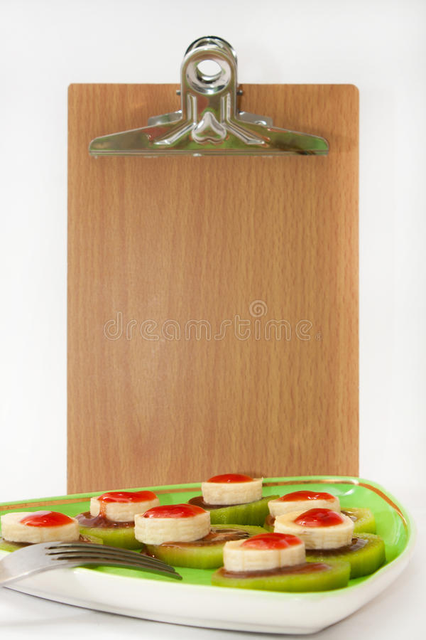Sliced banana and kiwi with strawberry syrup and message board.  stock images
