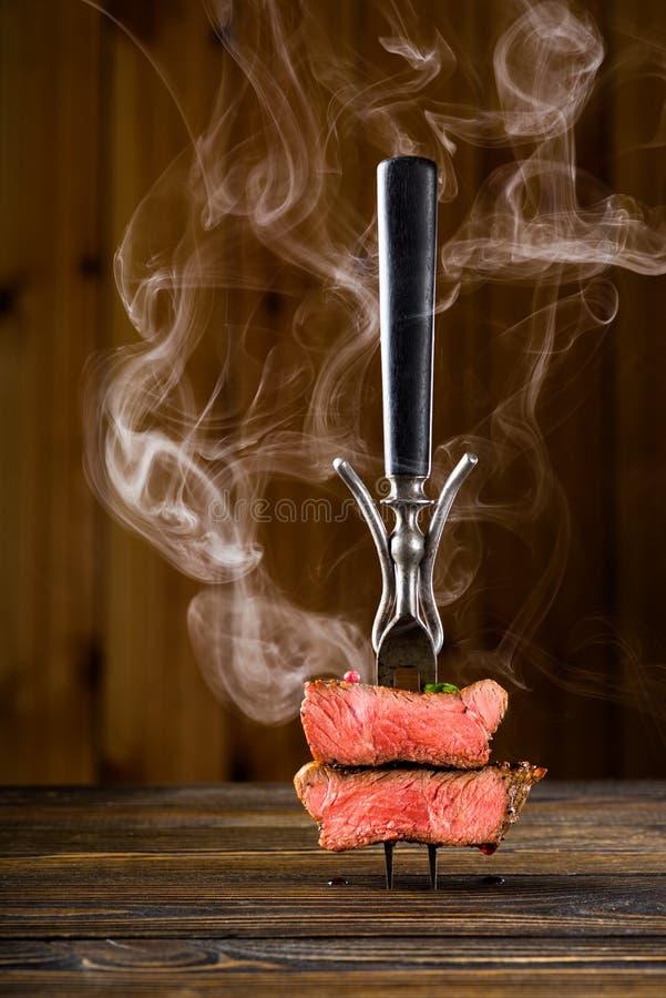 Sliced beef steak on a fork stock photos