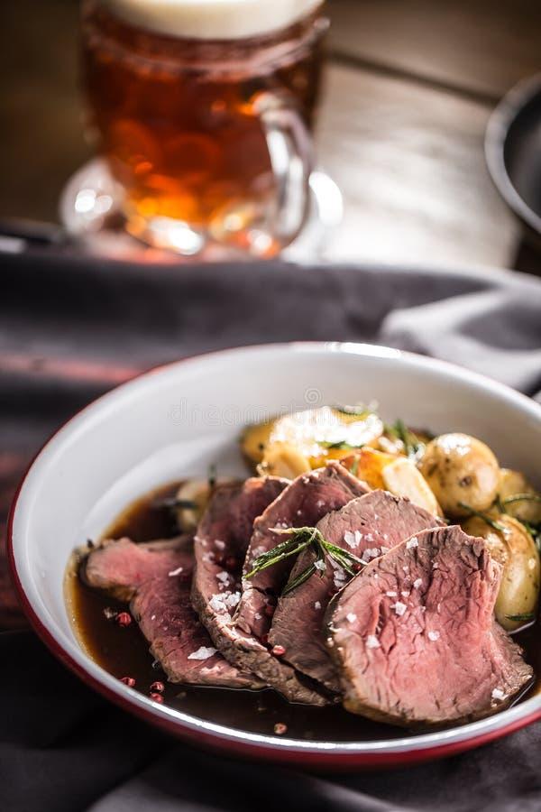 Sliced Beef tenderloin roasted steak potatoes rosemary and draft beer.  royalty free stock photos