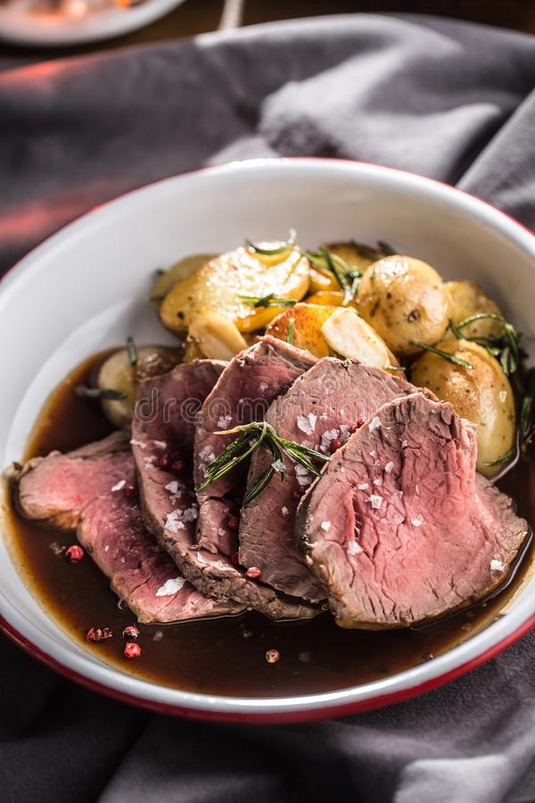 Sliced Beef tenderloin roasted steak potatoes rosemary and draft beer.  stock photos