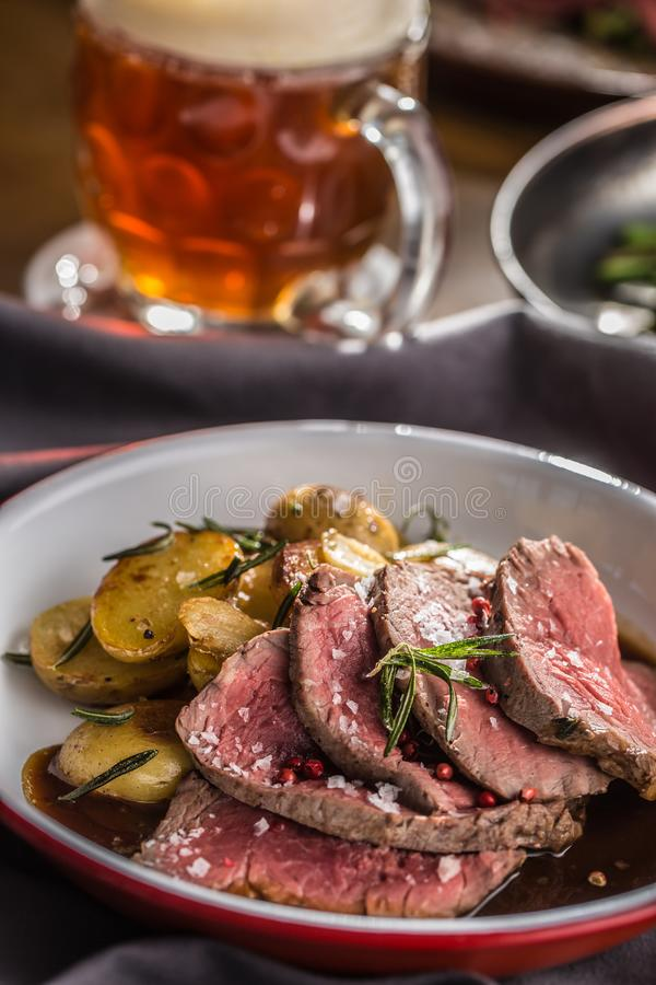 Sliced Beef tenderloin roasted steak potatoes rosemary and draft beer.  royalty free stock images