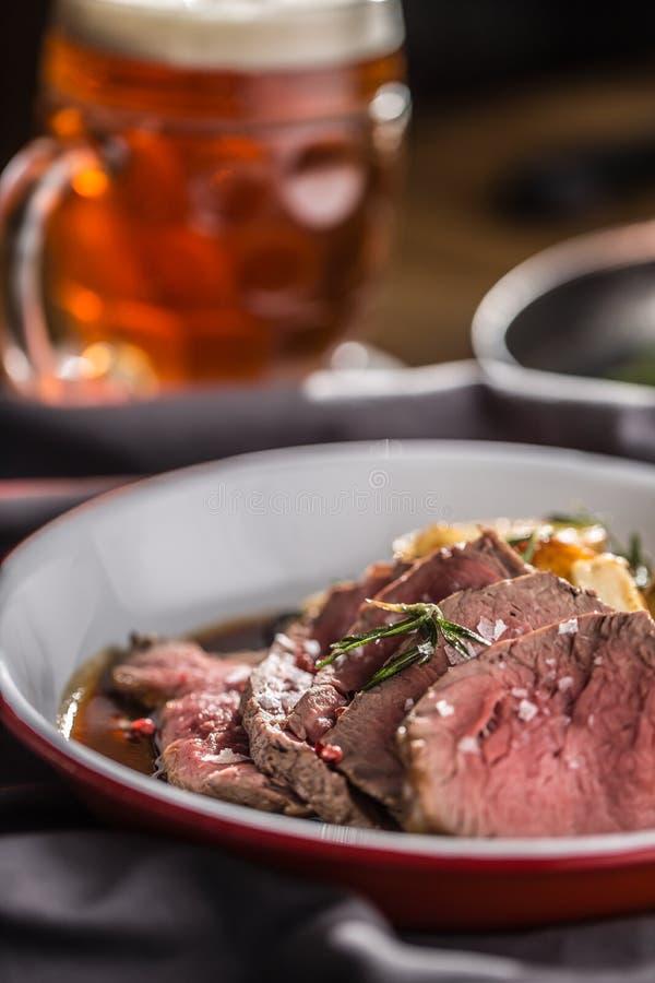 Sliced Beef tenderloin roasted steak potatoes rosemary and draft beer.  stock image