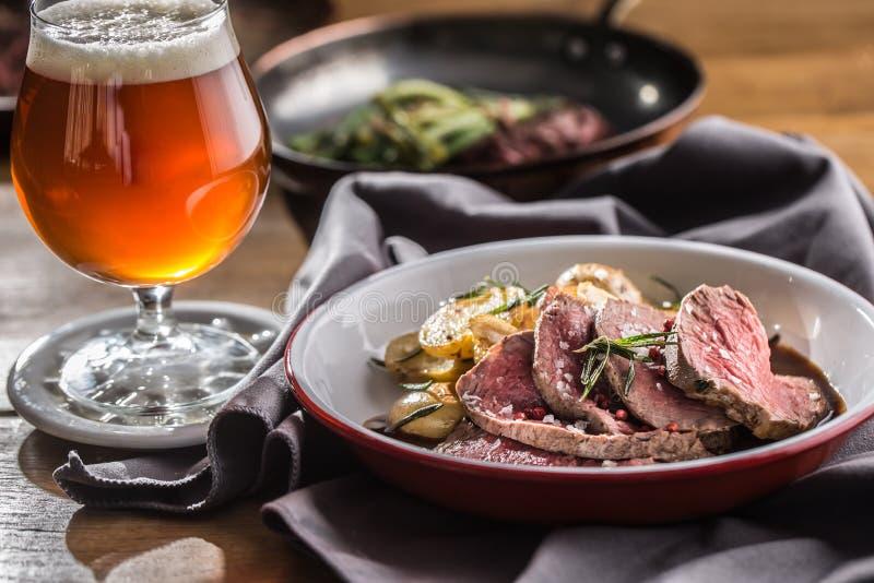 Sliced Beef tenderloin roasted steak potatoes rosemary and draft beer.  royalty free stock photo