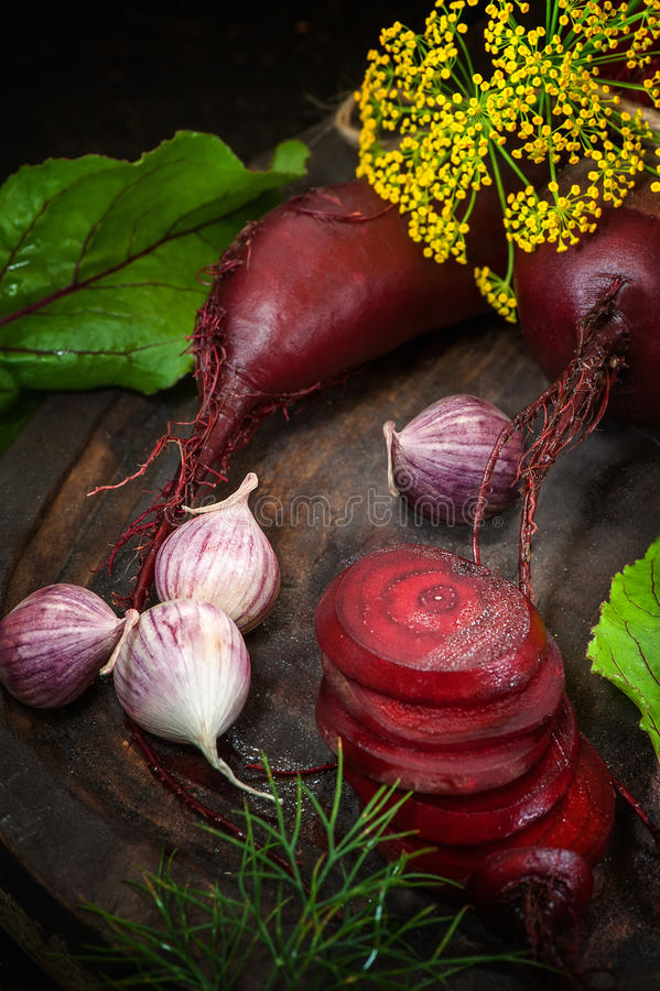 Sliced beets for making chips on a wooden Board with garlic and dill in a rustic style. The vertical frame royalty free stock photography