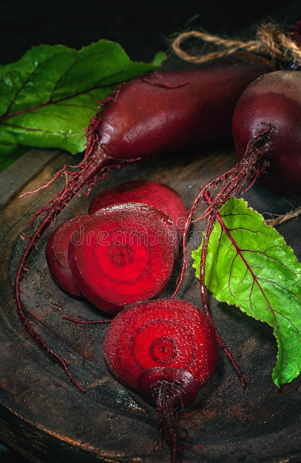 Sliced beets for making chips on a wooden Board in a rustic style. The vertical frame royalty free stock photos