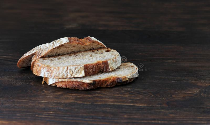 Sliced black bread, homemade rye bread on a old dark wooden background. Copy space. Healthy eating stock photo