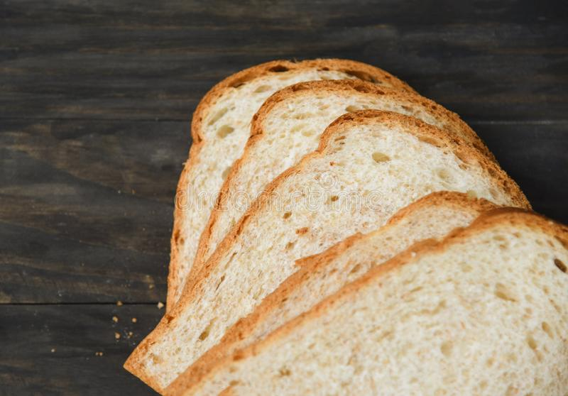 Sliced bread close up top view - Whole wheat bread cut on wooden dark. Sliced bread close up top view / Whole wheat bread cut on wooden dark stock photography