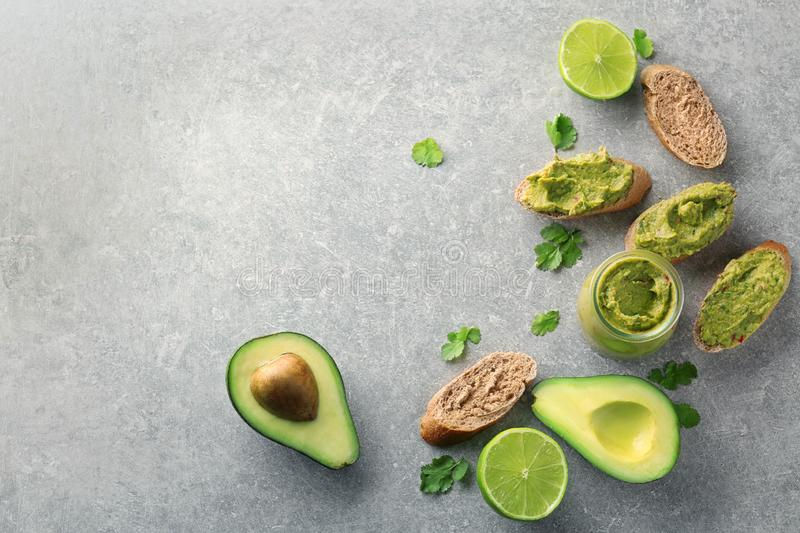 Sliced bread with delicious guacamole, lime and avocado on table stock images