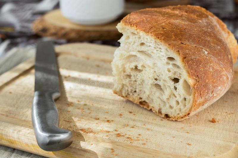 Sliced Bread and Stainless Steel Knife on Top of Brown Wooden Chopping Board stock photography