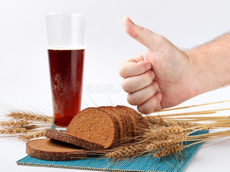 Sliced bread and wheat spikelets on bamboo mat with glass of soft drink. male hand with thumb up sign. white background royalty free stock photo