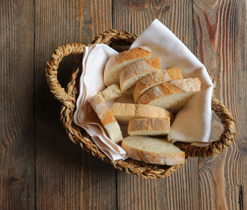 Sliced bread on a white napkin in straw basket. Rustic wooden table background royalty free stock images