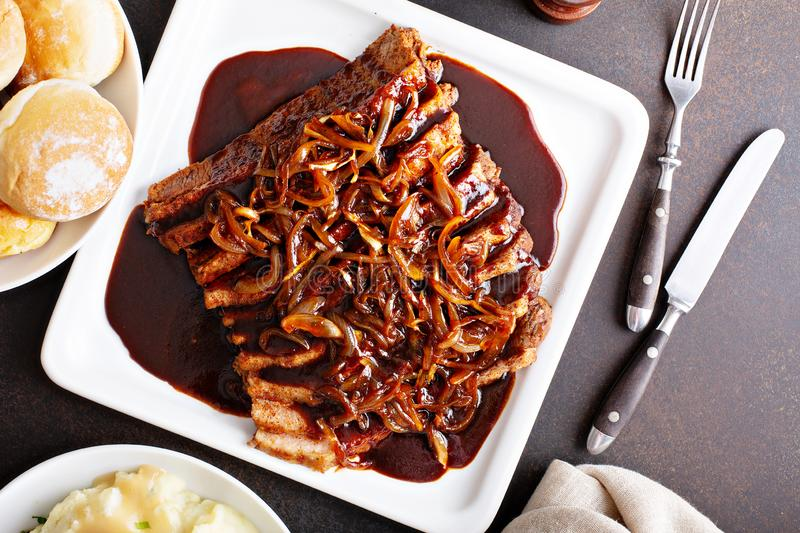 Sliced brisket with caramelized onions. Sliced brisket on a plate with caramelized onions royalty free stock images