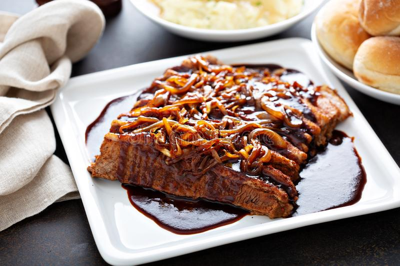 Sliced brisket with caramelized onions. Sliced brisket on a plate with caramelized onions stock photo