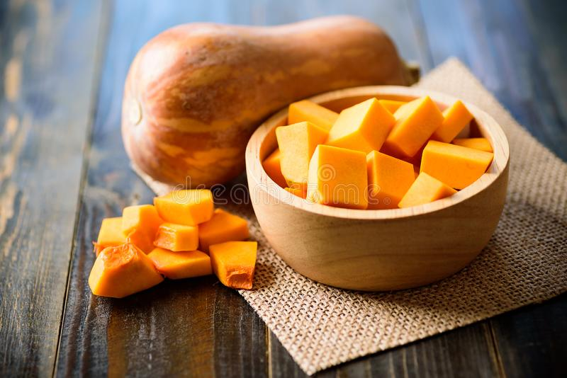 Sliced butternut squash in a bowl for cooking. On wooden background royalty free stock photography